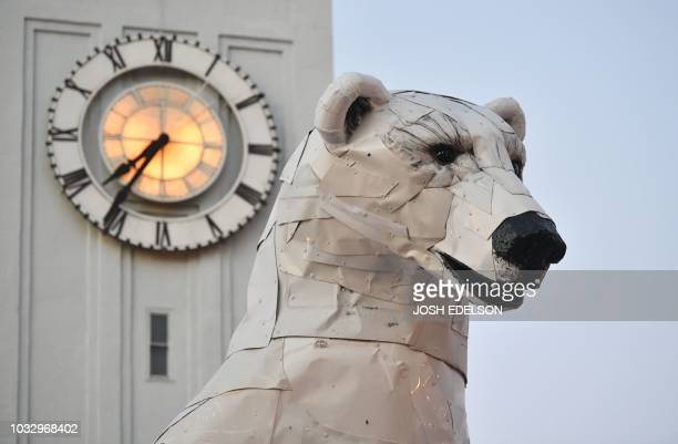 A polar bear statue made out of car hoods is seen during the Global Climate Action Summit in front of a clock in San Francisco California on...