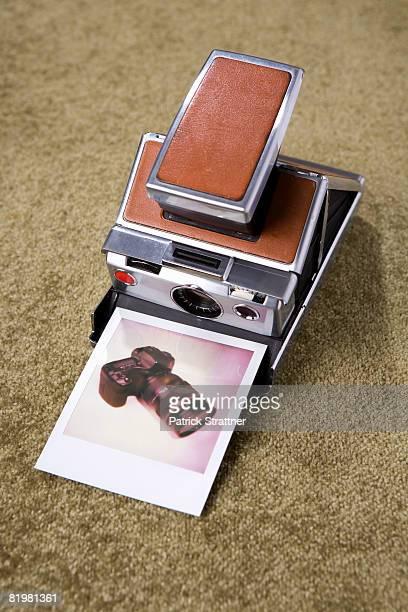 A Polaroid camera with a Polaroid picture of a digital camera