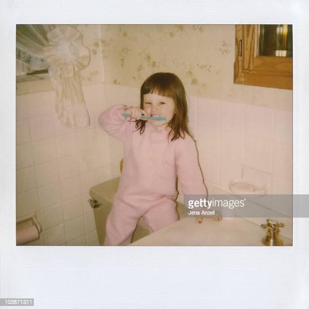Polaroid of a little girl brushing her teeth