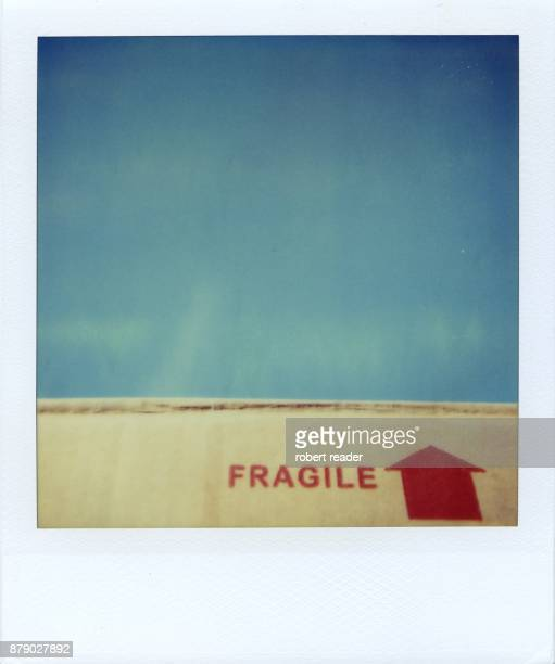 polaroid of cardboard box with fragile text against blue sky - fragile sign stock pictures, royalty-free photos & images