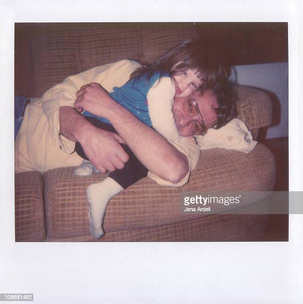 Polaroid of father and daughter hugging on couch
