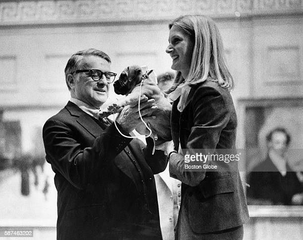 Polaroid's founder and chief executive Dr Edwin H Land cuddles one of two puppies presented him at the annual stockholders meeting in Boston on April...