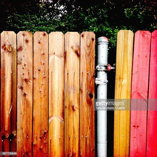 Pole Amidst Wooden Fence Against Trees