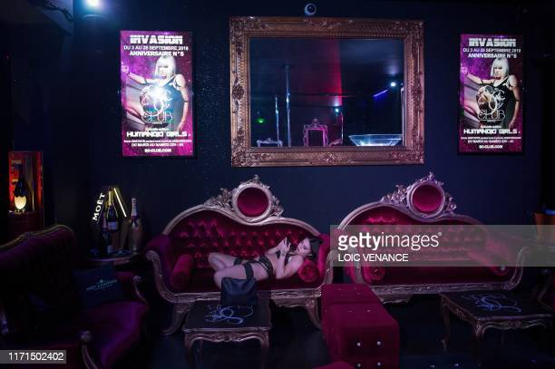 TOPSHOT A pole dancer looks at her phone prior to the start of her show at a pole dance club in Nantes western France on September 27 2019