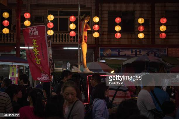 A pole dancer pauses between performances on the roof of a car during a parade near Xingang Fengtian Temple where the statue of Mazu will rest for...