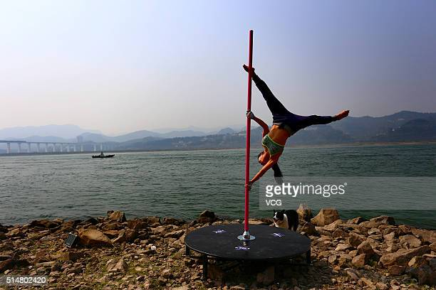 A pole dancer performs by the riverside of Yangtze River on March 11 2016 in Yichang Hubei Province of China It's said that the performance comes...