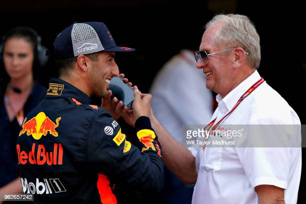 Pole position qualifier Daniel Ricciardo of Australia and Red Bull Racing talks on the phone with Red Bull Racing Team Consultant Dr Helmut Marko in...