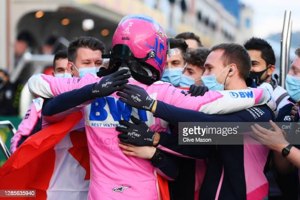 Pole position qualifier Lance Stroll of Canada and Racing Point celebrates with team members in parc ferme during qualifying ahead of the F1 Grand...