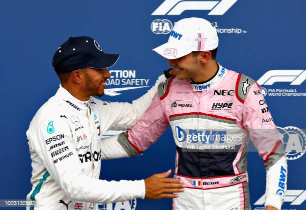 Pole position qualifier Lewis Hamilton of Great Britain and Mercedes GP congratulates third place qualifier Esteban Ocon of France and Force India in...