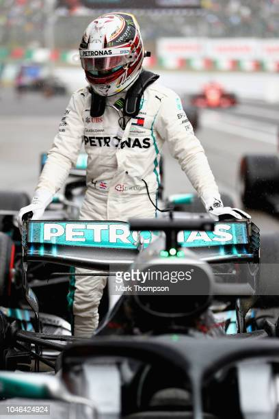 Pole position qualifier Lewis Hamilton of Great Britain and Mercedes GP climbs from his car in parc ferme during qualifying for the Formula One Grand...