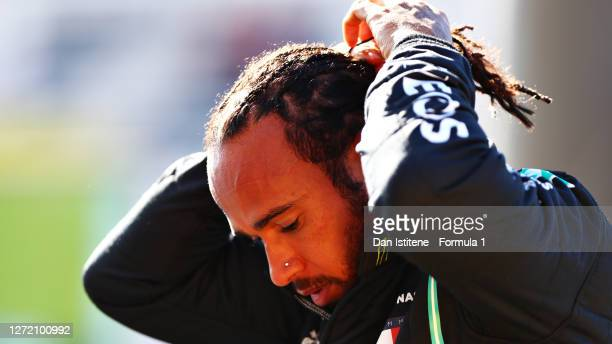 Pole position qualifier Lewis Hamilton of Great Britain and Mercedes GP looks on in parc ferme during qualifying for the F1 Grand Prix of Tuscany at...