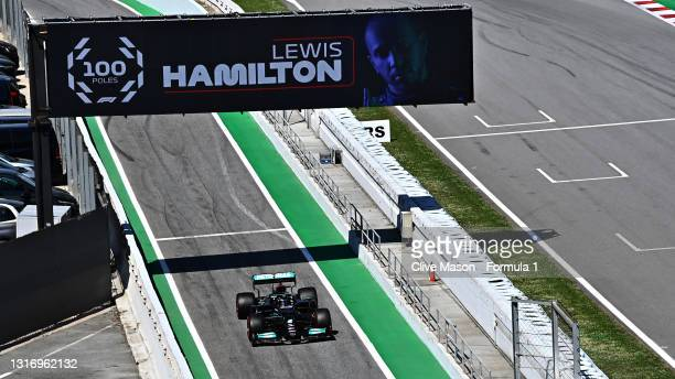 Pole position qualifier Lewis Hamilton of Great Britain and Mercedes GP pulls into parc ferme under a banner celebrating his 100 pole positions...