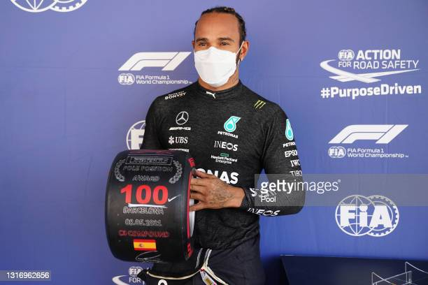 Pole position qualifier Lewis Hamilton of Great Britain and Mercedes GP celebrates with his pole position award in parc ferme after qualifying for...