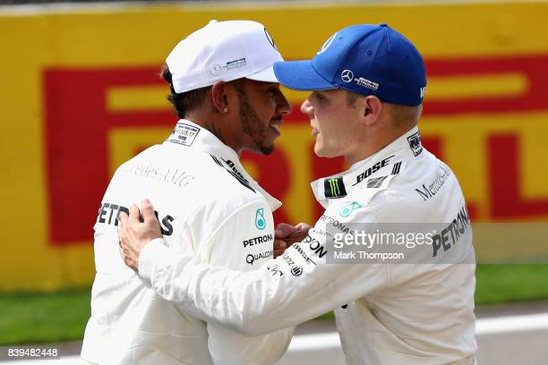 Pole position qualifier Lewis Hamilton of Great Britain and Mercedes GP is congratulated by third placed qualifier and teammate Valtteri Bottas of...
