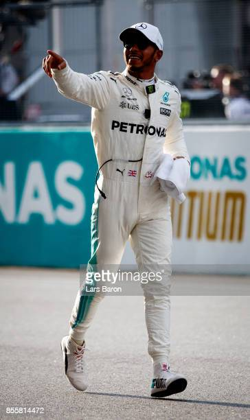 Pole position qualifier Lewis Hamilton of Great Britain and Mercedes GP celebrates in parc ferme during qualifying for the Malaysia Formula One Grand...