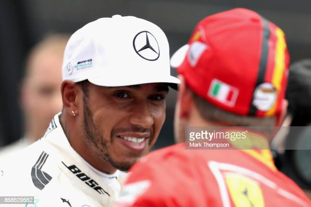 Pole position qualifier Lewis Hamilton of Great Britain and Mercedes GP with third place qualifier Sebastian Vettel of Germany and Ferrari in parc...