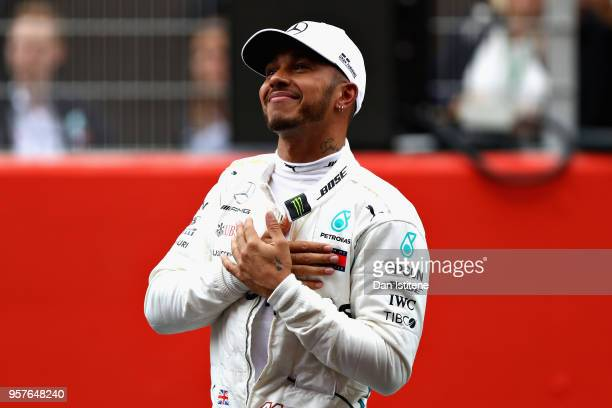 Pole position qualifier Lewis Hamilton of Great Britain and Mercedes GP celebrates in parc ferme during qualifying for the Spanish Formula One Grand...