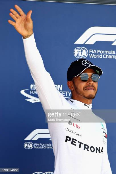 Pole position qualifier Lewis Hamilton of Great Britain and Mercedes waves to the crowd from parc ferme during qualifying for the Formula One Grand...