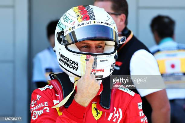 Pole position qualifier Sebastian Vettel of Germany and Ferrari celebrates in parc ferme during qualifying for the F1 Grand Prix of Japan at Suzuka...