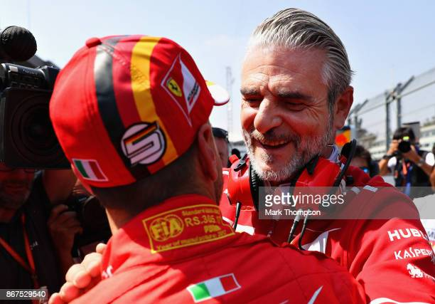 Pole position qualifier Sebastian Vettel of Germany and Ferrari is congratulated by Ferrari Team Principal Maurizio Arrivabene in parc ferme during...