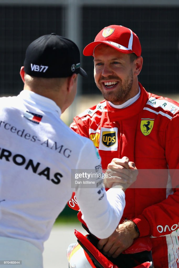 Pole position qualifier Sebastian Vettel of Germany and Ferrari shakes hands with second place qualifier Valtteri Bottas of Finland and Mercedes GP in parc ferme during qualifying for the Canadian Formula One Grand Prix at Circuit Gilles Villeneuve on June 9, 2018 in Montreal, Canada.
