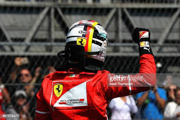 Pole position qualifier Sebastian Vettel of Germany and Ferrari waves to crowd from parc ferme during qualifying for the Formula One Grand Prix of...