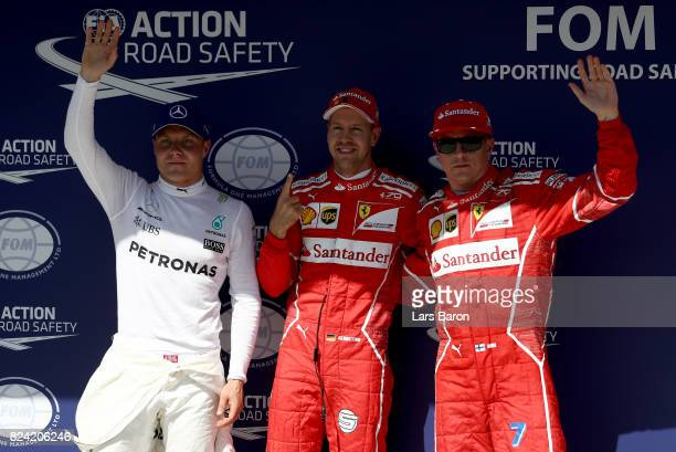 Pole position qualifier Sebastian Vettel of Germany and Ferrari with second place qualifier Kimi Raikkonen of Finland and Ferrari and third place...