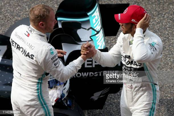 Pole position qualifier Valtteri Bottas of Finland and Mercedes GP shakes hands with second placed qualifier Lewis Hamilton of Great Britain and...