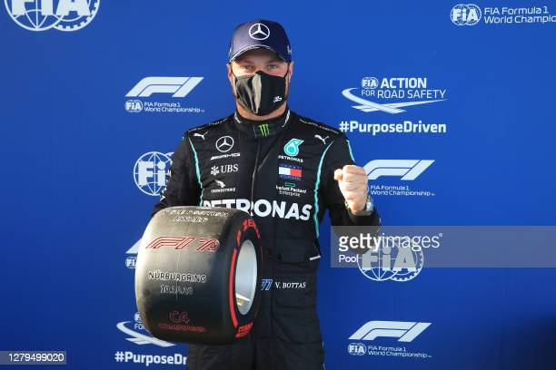 Pole position qualifier Valtteri Bottas of Finland and Mercedes GP celebrates in parc ferme during qualifying ahead of the F1 Eifel Grand Prix at...