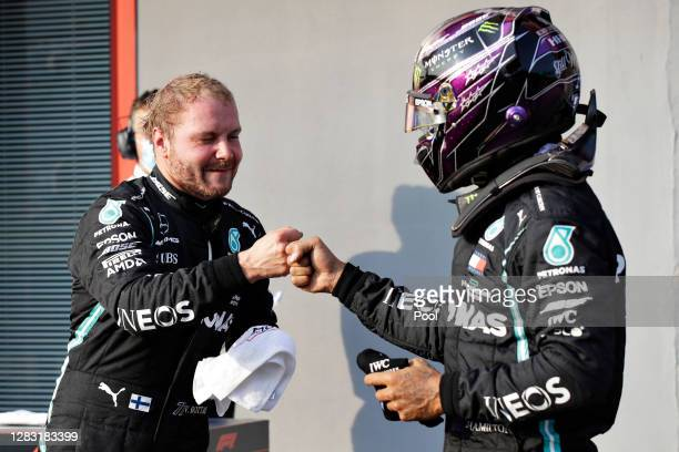Pole position qualifier Valtteri Bottas of Finland and Mercedes GP bumps fists with second place qualifier Lewis Hamilton of Great Britain and...
