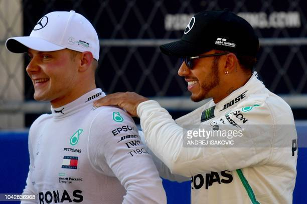 Pole position winner Mercedes' Finnish driver Valtteri Bottas and second positioned Mercedes' British driver Lewis Hamilton react after the...