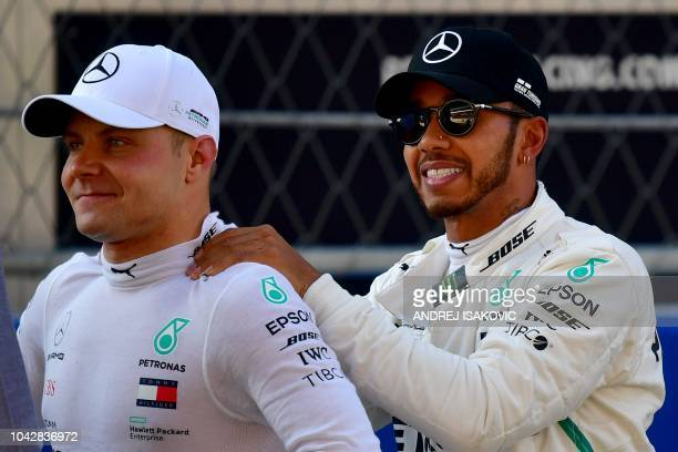 TOPSHOT Pole position winner Mercedes' Finnish driver Valtteri Bottas and second positioned Mercedes' British driver Lewis Hamilton react after the...