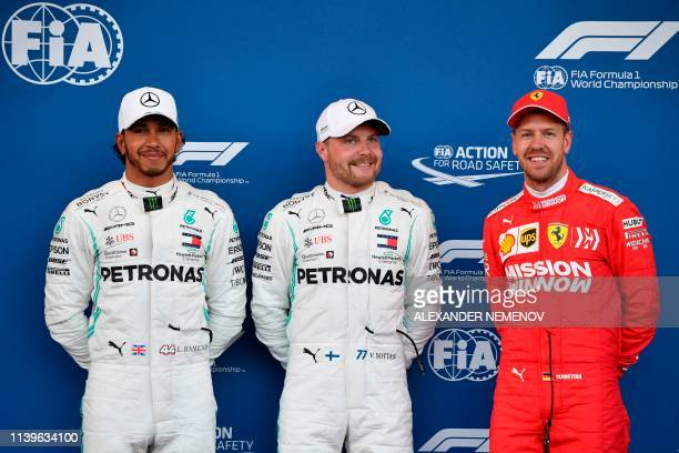 Pole position winner Mercedes' Finnish driver Valtteri Bottas poses with second placed Mercedes' British driver Lewis Hamilton and third placed...