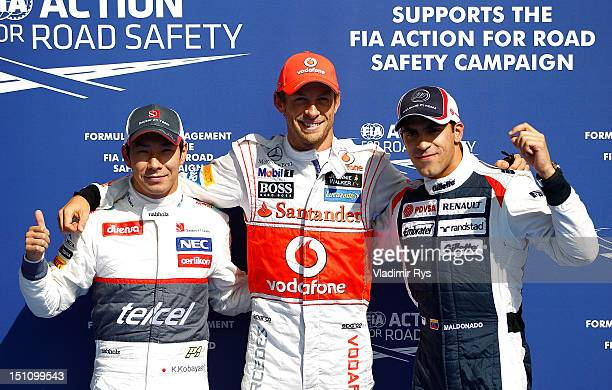 SPA FRANCORCHAMPS BELGIUM SEPTEMBER 01 Pole sitter Jenson Button of Great Britain and McLaren poses for a photo together with Kamui Kobayashi of...