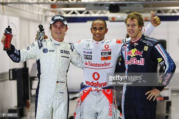 Pole sitter Lewis Hamilton of Great Britain and McLaren Mercedes celebrates with second placed Sebastian Vettel of Germany and Red Bull Racing and...