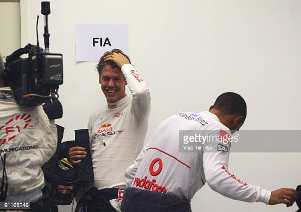 Pole sitter Lewis Hamilton of Great Britain and McLaren Mercedes celebrates with second placed Sebastian Vettel of Germany and Red Bull Racing in...