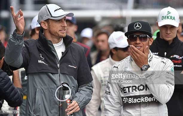 Pole sitter Mercedes driver Lewis Hamilton of Britain walks down the pit lane talking with compatriot McLaren driver Jensen Button for the annual...