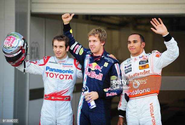 Pole sitter Sebastian Vettel of Germany and Red Bull Racing celebrates with second placed Jarno Trulli of Italy and Toyota and third placed Lewis...