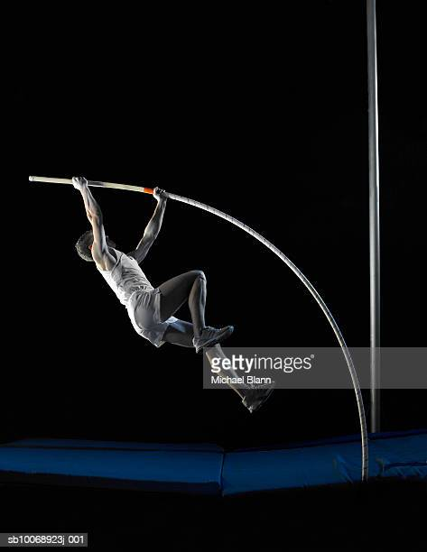 Pole vault athlete jumping, side view