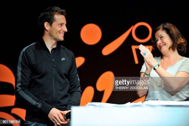 Pole vault European champion Renaud Lavillenie is applauded by Michelin's public relations manager Claire DorlandClauzel during Michelin's...