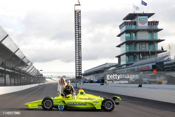 Pole winner IndyCar driver Simon Pagenaud of the Menards Team Penske Chevrolet and his fiancee Hailey McDermott along with their dog Norman during...