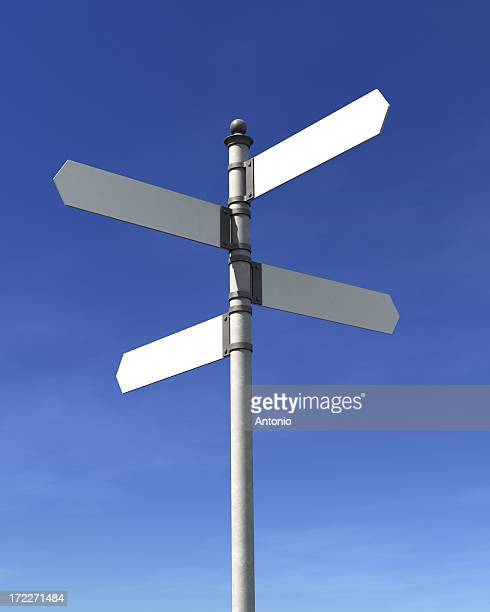 a pole with 4 blank street signs pointing at 4 directions - richting stockfoto's en -beelden