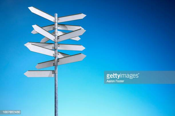 a 3d pole with blank street signs pointing all directions - richtung stock-fotos und bilder