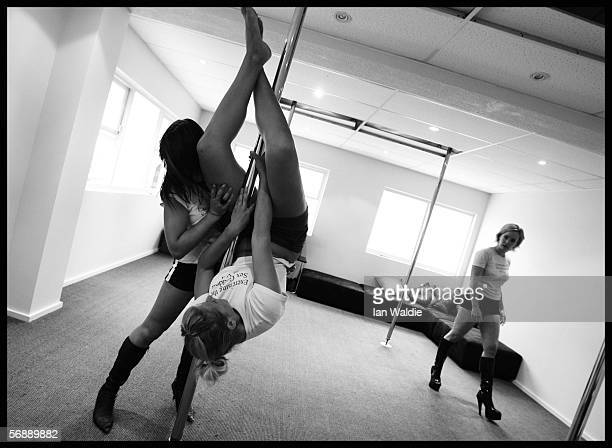 Poledancing student Charlotte Priestley gets advice on a move from Polestars Australia instructor Stephanie Kite as fellow student Danielle Grimmond...