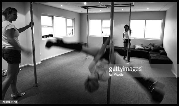 Poledancing students Danielle Grimmond and Charlotte Priestley practice moves on dance poles as Polestars Australia instructor Stephanie Kite looks...