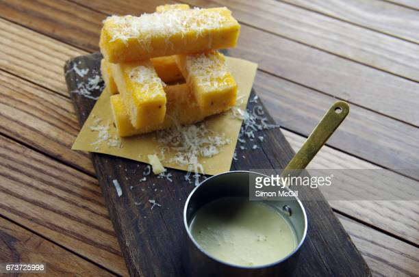 polenta fritta - truffled polenta chips served with a gorgonzola cheese sauce - cheese sauce stock photos and pictures