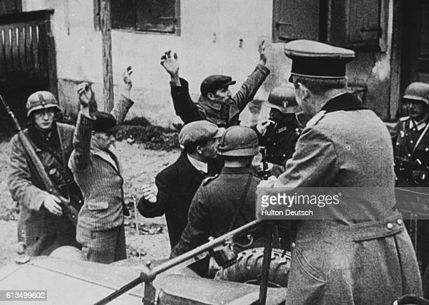 Poles are searched by SS soldiers at a Gestapo headquarters in Poland