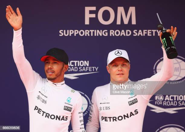 Polesitter Lewis Hamilton of Great Britain and Mercedes GP and 3rd place qualifier Valtteri Bottas of Finland and Mercedes GP wave to the crowd from...