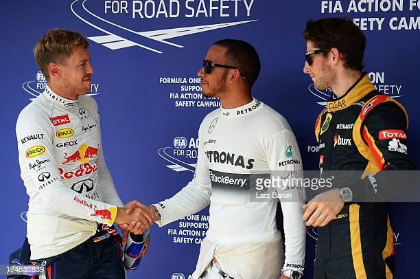 Polesitter Lewis Hamilton of Great Britain and Mercedes GP celebrates with second placed Sebastian Vettel of Germany and Infiniti Red Bull Racing and...