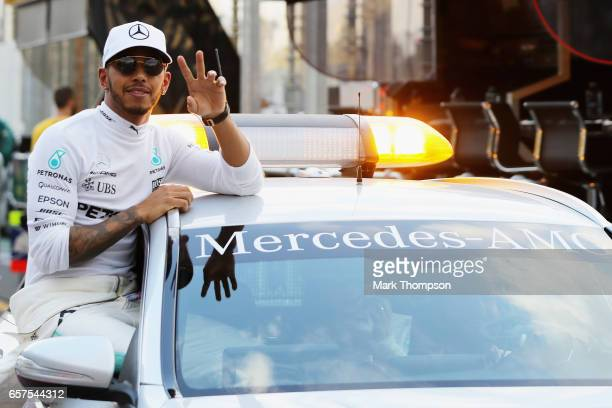 Polesitter Lewis Hamilton of Great Britain and Mercedes GP celebrates in parc ferme during qualifying for the Australian Formula One Grand Prix at...